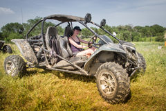 Buggy car at green field. Young woman driving, Almaty, Kazakhsta. N Stock Photography