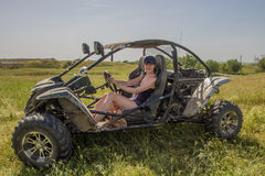 Buggy car at green field. Young woman driving, Almaty, Kazakhsta. N Royalty Free Stock Image