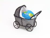Buggy de bebê com a terra do planeta dentro fotografia de stock