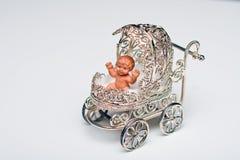 Buggy de bebê de prata diminuto que contem o infante Fotografia de Stock Royalty Free