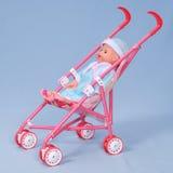 Buggy de bebê do brinquedo no fundo azul. imagem de stock royalty free