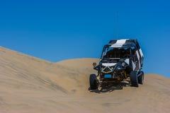 Buggy des sables au-dessus d'une dune de sable dans le désert, Huacachina, AIC, Pérou photo libre de droits