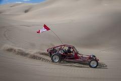 Buggy des sables rouge de sable emballant par dans les dunes de sable Image stock
