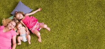 Bugia bambini di due e della madre su tappeto Immagini Stock Libere da Diritti
