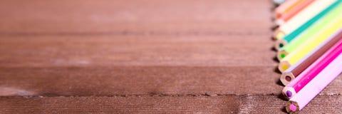Bugia colorata delle matite sull'orlo di un bordo di legno Fotografie Stock Libere da Diritti