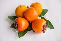 Bugia del cachi e dell'arancia su un piatto Fotografie Stock