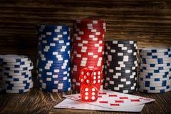 Bugia del cubo della mazza di due rossi sulle carte contro lo sfondo dei chip di mazza Immagine Stock Libera da Diritti