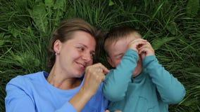 Bugia del figlio e della madre sull'erba e sulle sciocchezze intorno, divertendosi, ridendo archivi video