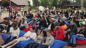 Bugia della gente sui beanbags enormi in parco Festival di estate Palloni di Wave pubblici video d archivio