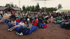 Bugia della gente sui beanbags enormi sulla sabbia Festival di estate Orizzontale della pentola pubblici archivi video