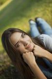 Bugia della giovane donna su erba in parco Fotografie Stock