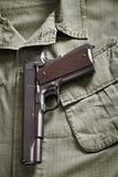 Bugia della pistola del puledro sul rivestimento militare Immagine Stock