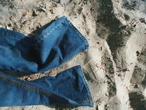 Bugia delle blue jeans sulla sabbia Fotografie Stock Libere da Diritti