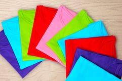 bugia delle magliette di donne colorate Multi su fondo di legno Fotografie Stock Libere da Diritti