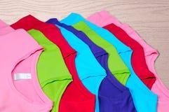 bugia delle magliette di donne colorate Multi su fondo di legno Fotografia Stock Libera da Diritti