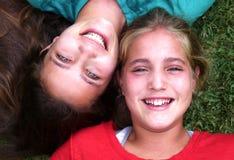 Bugia di due una giovane sorelle su erba Fotografia Stock