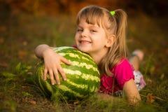 Bugia felice della ragazza del bambino sull'anguria molto grande dell'abbraccio e dell'erba nel giorno soleggiato immagini stock libere da diritti