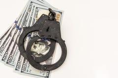 Bugia nera delle manette del metallo su 100 banconote in dollari Fotografia Stock