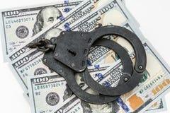 Bugia nera delle manette del metallo su 100 banconote in dollari Fotografie Stock