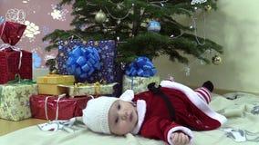 Bugia sveglia della neonata vicino all'albero di Natale ed ai contenitori attuali di regalo stock footage