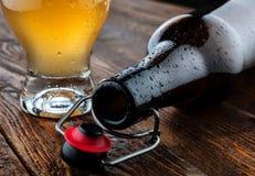 Bugia vuota della bottiglia vicino a birra di vetro Immagine Stock