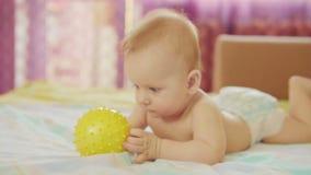 Bugie belle di un bambino Tiene la palla in sua mano ed i giochi con  video d archivio