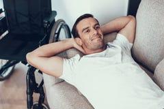Bugie belle sorridenti dell'uomo su Sofa Near Wheelchair fotografia stock libera da diritti