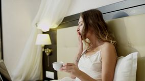 Bugie della giovane donna a letto, caffè delle bevande ed avere una video chiacchierata sopra il suo computer portatile video d archivio