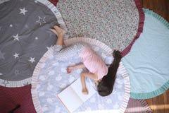 Bugie e sonni della ragazza del bambino sulla stuoia accanto all'album fotografia stock libera da diritti