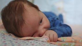 Bugie infantili sul suo stomaco con i grandi occhi aperti su un letto per i neonati archivi video