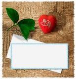 Bugie rosse luminose di un cuore su un fondo di legno con una foglia bianca di carta e delle foglie verdi Cartolina d'auguri per  fotografia stock