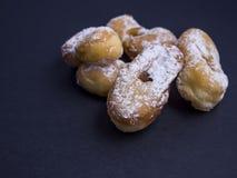 Bugnes, французский тип печенье донута покрытое при напудренный сахар изолированный на черноте Стоковая Фотография