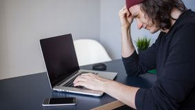 Bugs and errors in the development. A young programmer in the workplace has problems at work. A young man sitting at a table with a laptop royalty free stock images