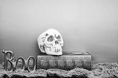 Buh und Schädel mit Halloween-Buch von den Bannen Schwarzweiss Stockbilder