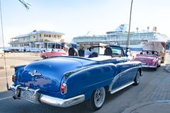 Buick azul, Chevrolet cor-de-rosa, carros convertíveis clássicos americanos, na frente do terminal do cruzeiro em Havana, Cuba fotos de stock