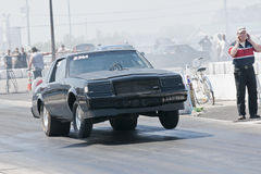 Buick drag car. Picture of black buick regal with two front wheels up during drag race at napierville dragway Royalty Free Stock Images