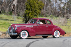 1940 Buick Special Coupe driving on country road. Adelaide, Australia - September 25, 2016: Vintage 1940 Buick Special Coupe driving on country roads near the royalty free stock photo