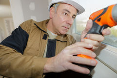 Buider using drill for installation new window. Buider using drill for the installation of a new window royalty free stock photography