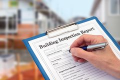 Buiding Inspector completing an inspection form on clipboard. Beside new build construction stock images