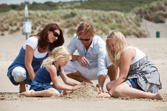 Buidling a sandcastle together. Attractive family sitting together on the beach building a sandcastle Royalty Free Stock Photography