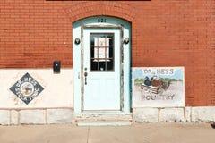 Buidlings Dr Hess höns och bleknad grön dörr i tegelstenexter Arkivfoto