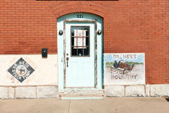 Buidlings,  Dr. Hess Poultry and faded green door in brick exter Stock Photo