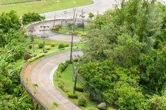 3 buigen betonweg zijn dalen van heuvel samen met bos Stock Afbeeldingen