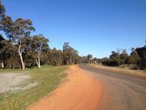 Buigende weg met bomen, zand en blauwe hemel in Westelijk Australië royalty-vrije stock fotografie