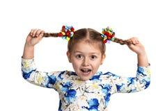 Buigt het studio dichte omhooggaande portret van een klein meisje die overhemd met een druk en met twee vlechten en kleur dragen  royalty-vrije stock foto