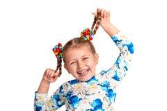 Buigt het studio dichte omhooggaande portret van een klein meisje die overhemd met een druk en met twee vlechten en kleur dragen  stock fotografie