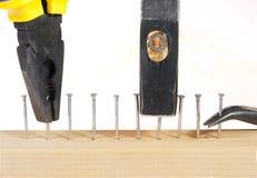 Buigtang en hamer met spijkers in houten plank. stock afbeeldingen