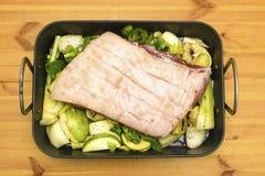 Buik die van varkensvlees op een treeft van groenten rusten Stock Afbeelding