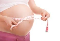 Buik van zwangere vrouwenmeting van band Stock Foto's