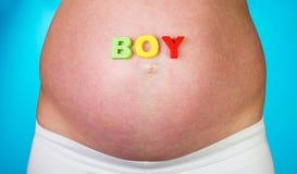 Buik zwangere vrouw met woordjongen op blauwe achtergrond Royalty-vrije Stock Afbeeldingen
